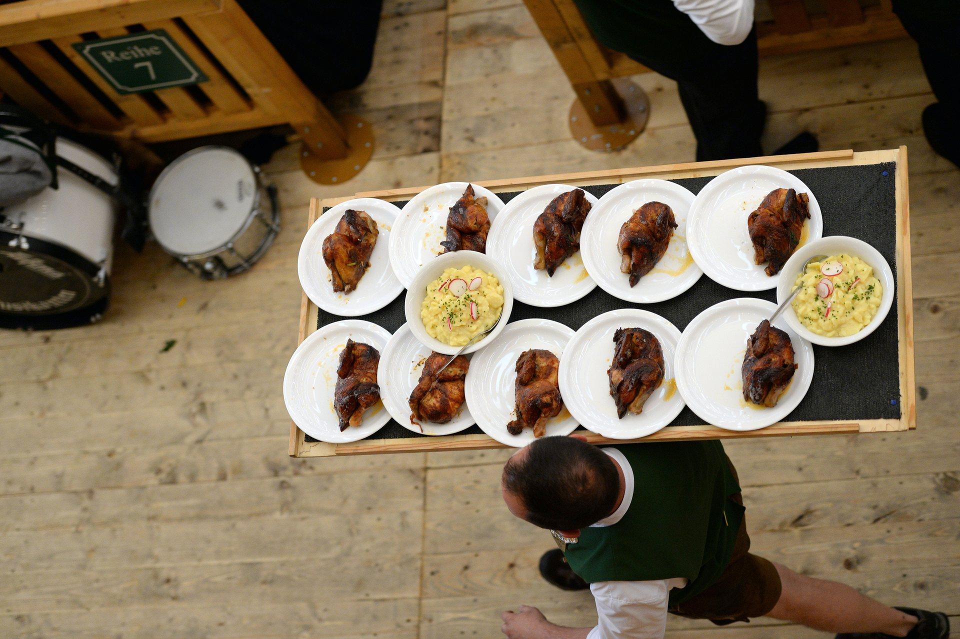 Официанты носят огромные подносы с курицей и картошкой в каждом из 34 тентов, в которых проходит «Октоберфест». Фото: Picture-Alliance/Barcroft Images