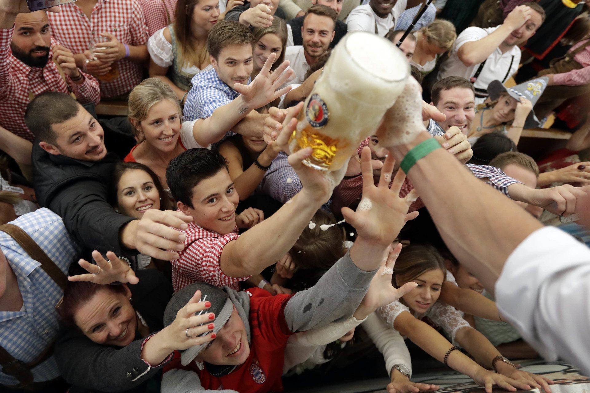 Первые бокалы пива раздаются бесплатно. Фото: Matthias Schrader/AP